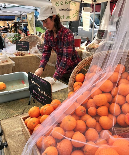 A Sweet Tree Farms team member selling mandarin oranges at the Hollywood CA farmers market.